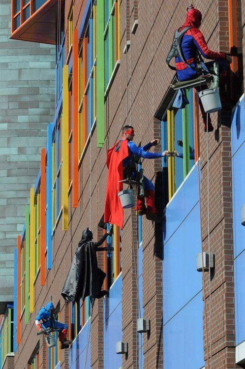 superheroes limpian ventanas de hospital