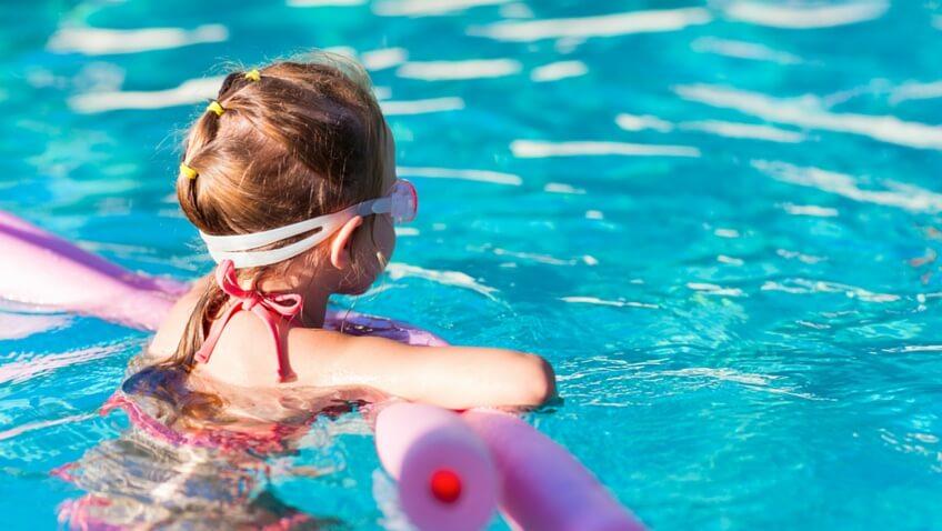 niña en la piscina con gafas de agua y bañador