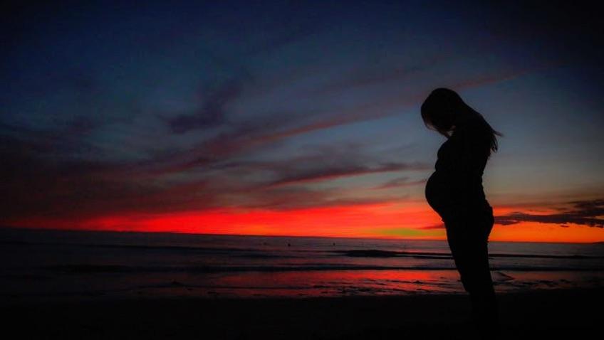 embarazada en verano en el mar atardeciendo