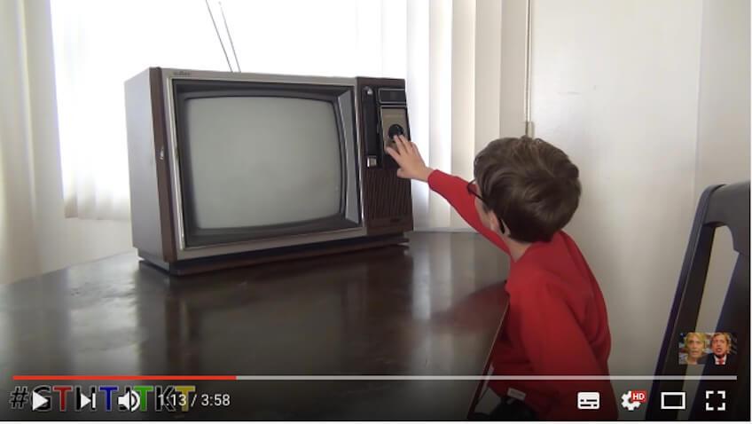 niño jugando televisor antiguo con botones