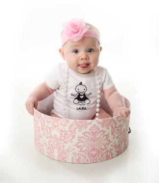 bebé con lazo roza y body dentro de una caja