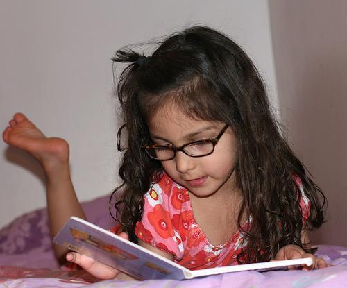 niña leyendo un libro en la cama