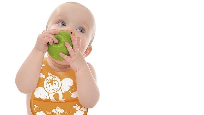 bebe comiendo manzana con babero de silicona naranja