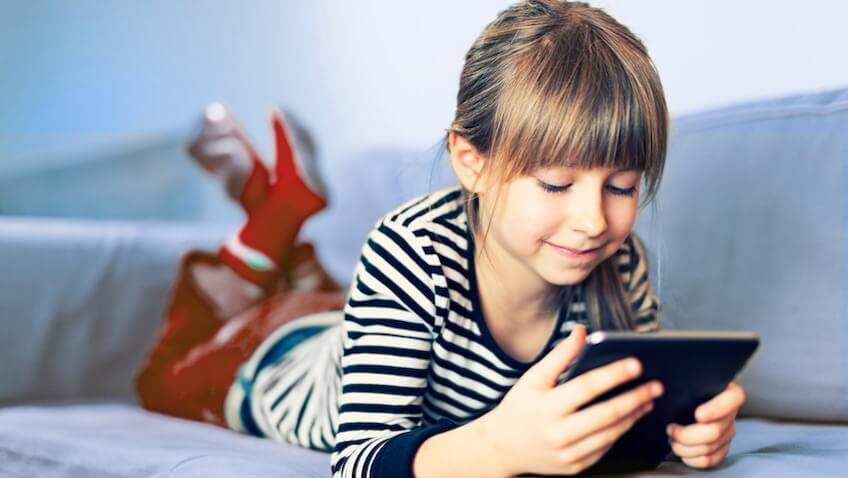 niña con tablet en un sofá