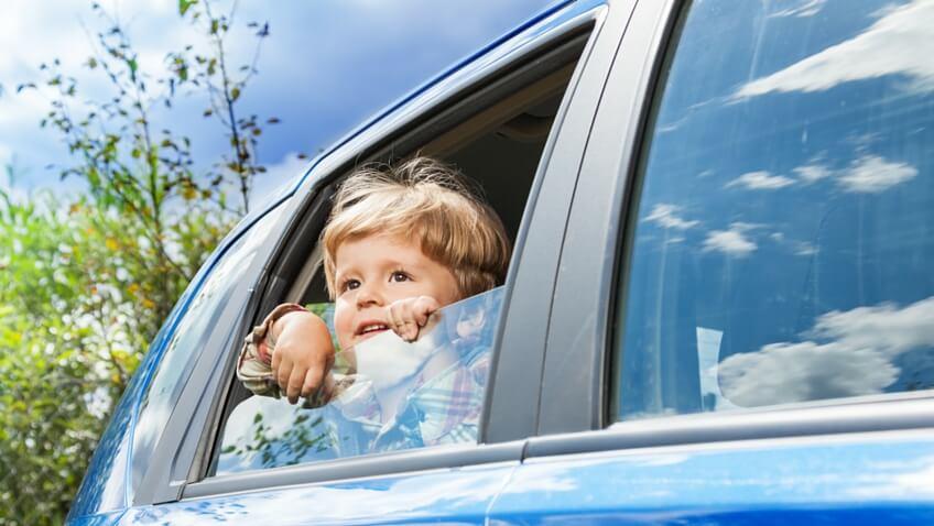 niño ventana coche azul