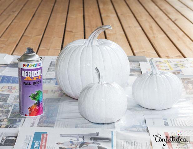 Hacer calabazas de unicornios Primer paso pintar las calabazas de color blanco con pintura en spray